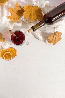 Een kopje glühwein met kruiden, fles, een sjaal, droge bladeren en sinaasappelen op de tafel. herfststemming, een methode om warm te blijven in de kou, copyspace.
