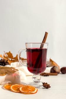 Een kopje glühwein met kruiden, sjaal, specerijen, droge bladeren en sinaasappelen op de tafel. herfststemming, een methode om warm te blijven in de kou, copyspace.