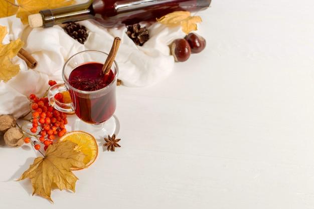 Een kopje glühwein met specerijen, fles, sjaal, specerijen, droge bladeren en sinaasappelen op tafel. herfststemming, methode om warm te blijven in de kou, copyspace.
