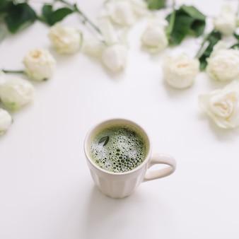 Een kopje groene matcha thee met witte rozen op wit uitzicht van bovenaf