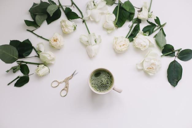 Een kopje groene thee met witte rozen op wit uitzicht van bovenaf. flatlay, bovenaanzicht, kopieerruimte.