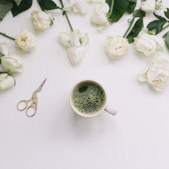 Een kopje groene thee met witte rozen op wit