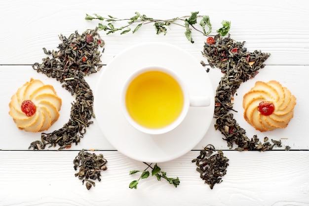 Een kopje groene thee op witte planken