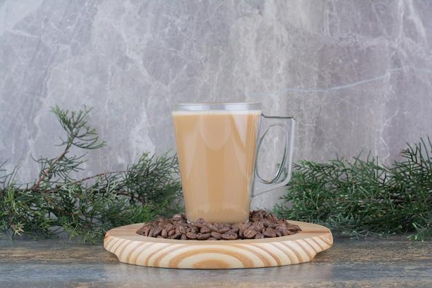 Een kopje heerlijke koffie met koffiebonen op een houten bord. hoge kwaliteit foto