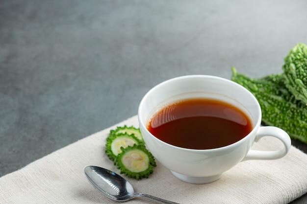 Een kopje hete bittere kalebas thee met rauwe gesneden bittere kalebas plaats op witte stof