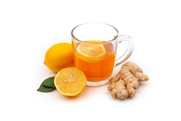 Een kopje hete zwarte of groene thee met citroen en gember op een witte achtergrond. ingrediënten tegen griep en virussen.