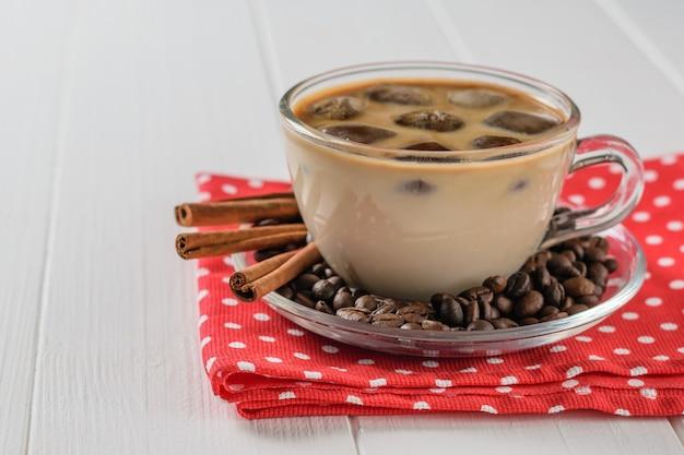 Een kopje ijskoffie en kaneel op een rode doek op een witte houten tafel. verfrissende en verkwikkende drank van koffiebonen en melk.