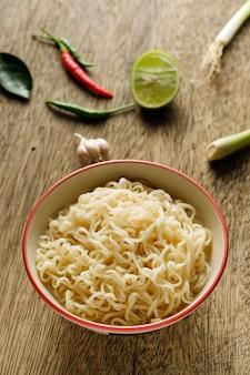 Een kopje instant noedels op een houten tafel geplaatst met limoen, chili, citroengras en knoflook als ingrediënten noodle
