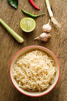 Een kopje instant noedels op een houten tafel met limoen, chili, citroengras en knoflook als ingrediënten, bovenaanzicht noodle