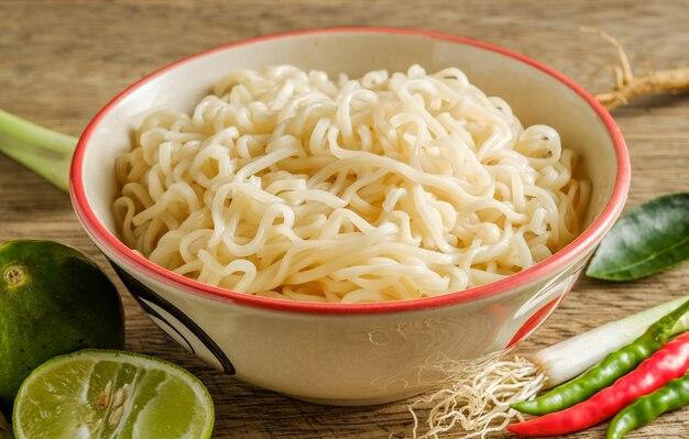 Een kopje instant noedels op een houten tafel met limoen, chili en knoflook als ingrediënten