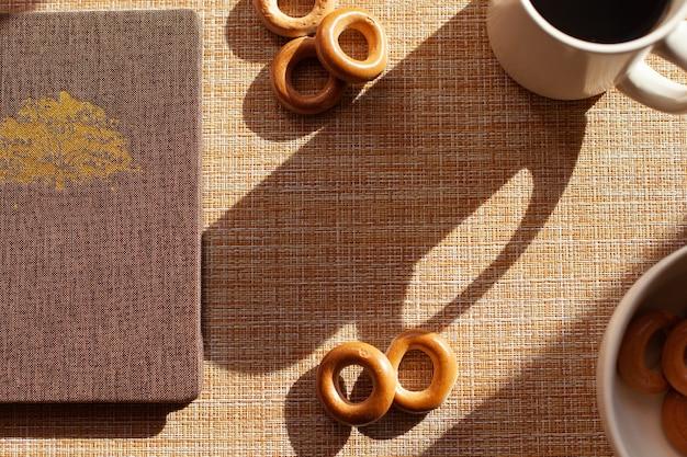 Een kopje koffie, baranki's, blocnote op houten tafel.