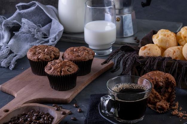 Een kopje koffie, chocolademuffins, kaasbroodjes en melk.
