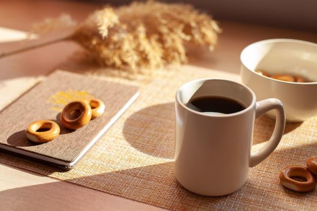 Een kopje koffie, droge bloemen, baranki's, blocnote op houten tafel.