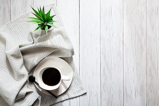 Een kopje koffie een licht servet en een vetplant in een witte pot op een lichte tafel