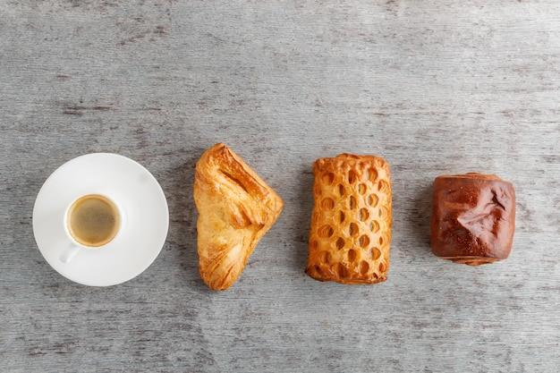Een kopje koffie en broodjes op een rij op een houten achtergrond.