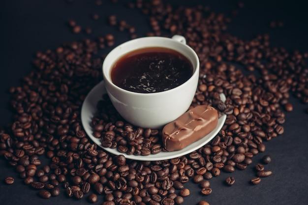 Een kopje koffie en een chocoladereep op een schoteltje arabica bonen