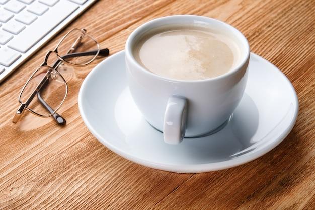 Een kopje koffie en een computer op de tafel. desktop van een zakenman. thuiswerken.