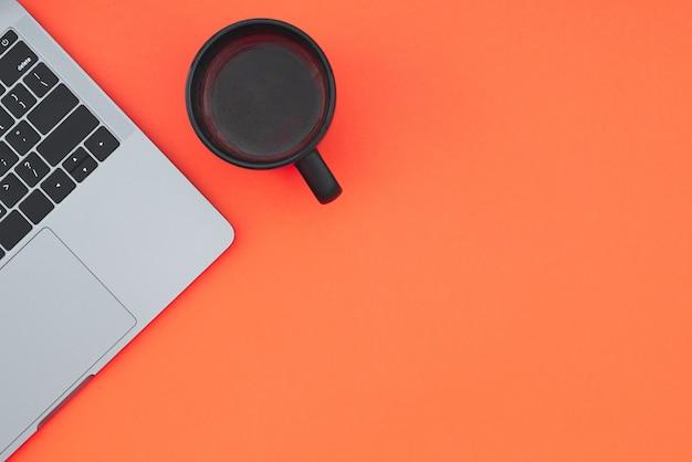 Een kopje koffie en een moderne notebook zijn geïsoleerd op een rode ondergrond
