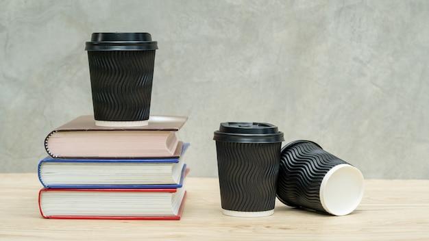 Een kopje koffie en een stapel van een boek op een houten tafel.