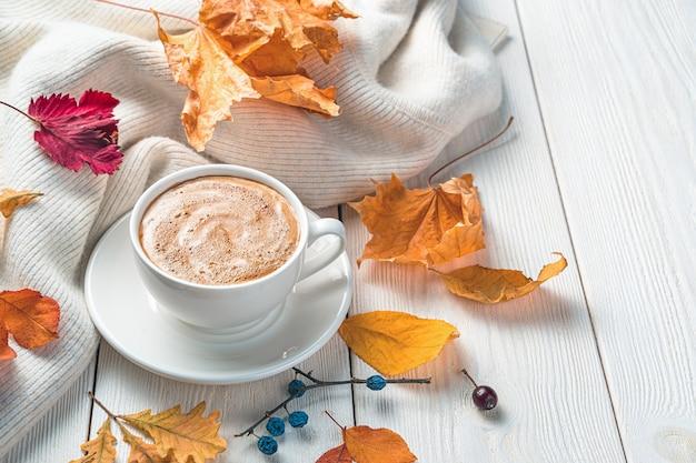 Een kopje koffie en een trui op een herfstachtergrond