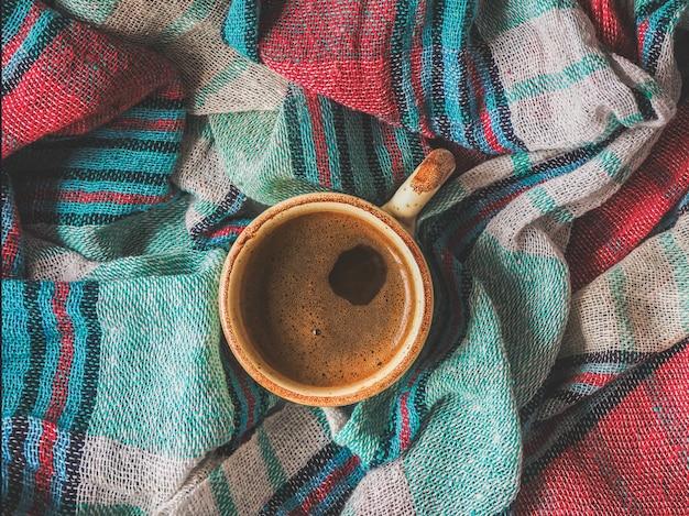 Een kopje koffie en gekleurd textiel. comfort op koude dagen. thuis comfort.
