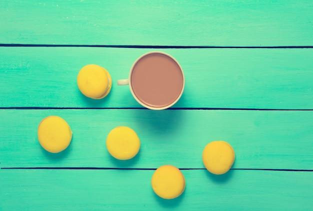 Een kopje koffie en gele bitterkoekjes op een blauwe houten tafel.