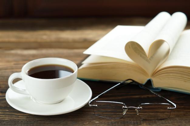 Een kopje koffie en hart boek met een bril op houten tafel