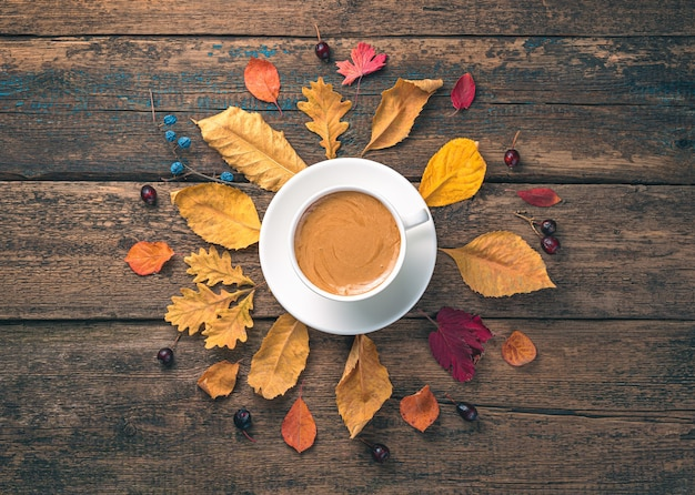 Een kopje koffie en herfstbladeren op een houten ondergrond