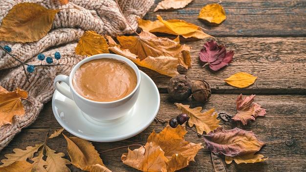Een kopje koffie en herfstgebladerte op een bruine houten ondergrond