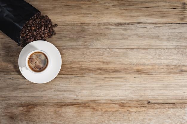 Een kopje koffie en koffiebonen op tafel. bovenaanzicht. kopieer de ruimte van uw tekst.