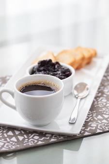 Een kopje koffie en toast met veenbessen jam op wit.