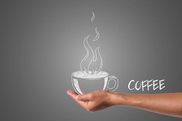 Een kopje koffie geschreven in wit krijt in zijn hand, tekenen concept.