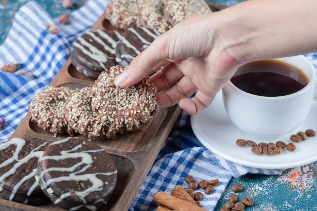 Een kopje koffie geserveerd met chocoladekoekjes.