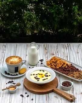 Een kopje koffie geserveerd met melk en dessert