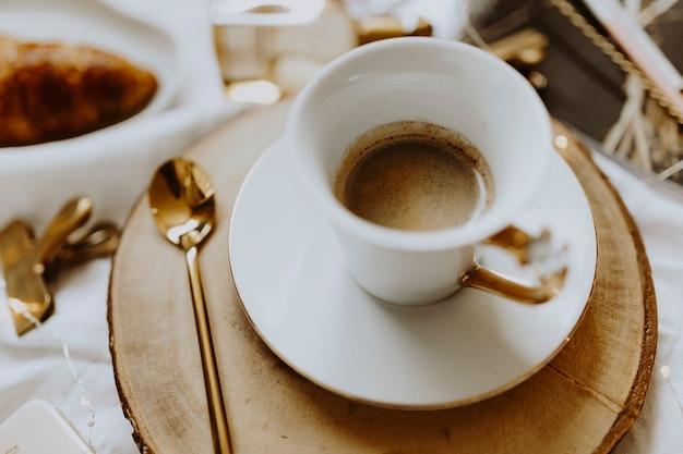 Een kopje koffie geserveerd op een houten dienblad