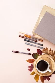 Een kopje koffie, herfstbladeren, boeken en gekleurde pennen op een lichte ondergrond bovenaanzicht.