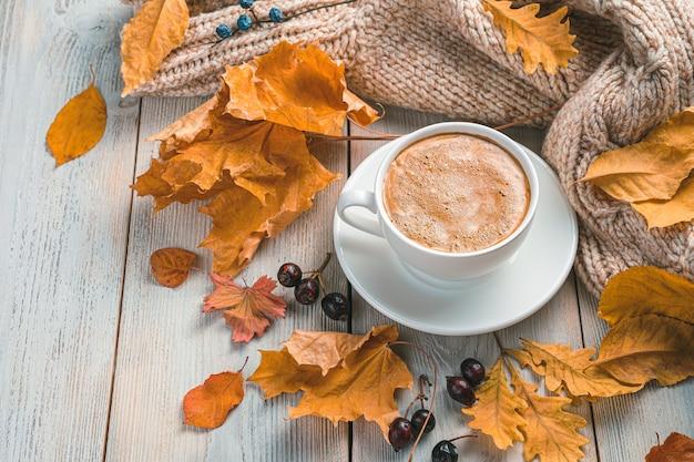 Een kopje koffie herfstbladeren en een gezellige trui op een beige achtergrond