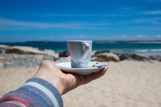 Een kopje koffie in de hand van de vrouw met uitzicht op het prachtige strand en de blauwe lucht