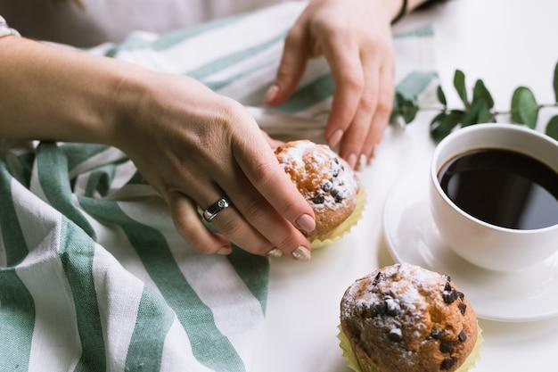 Een kopje koffie in de handen en muffins op een witte ondergrond en muffins