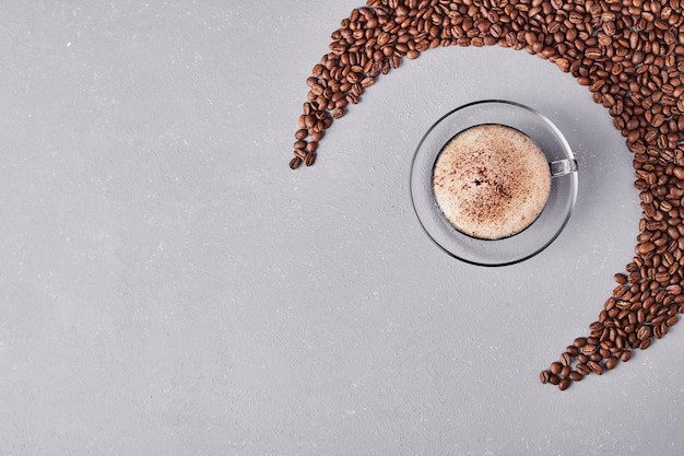 Een kopje koffie in een glazen schotel.