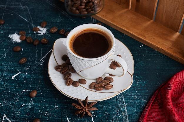 Een kopje koffie in een keramiek schotel.