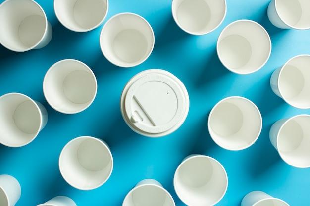 Een kopje koffie is omgeven door lege papieren bekers voor drankjes op een blauwe ruimte. conceptvriendelijk team, leider, directeur, baas. banner.