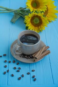 Een kopje koffie kaneel en zonnebloem op een blauwe achtergrond.