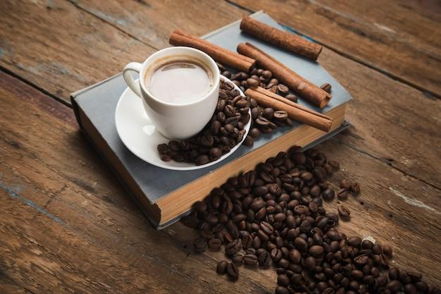 Een kopje koffie, koffiezaden, kaneel en een boek op een houten tafel