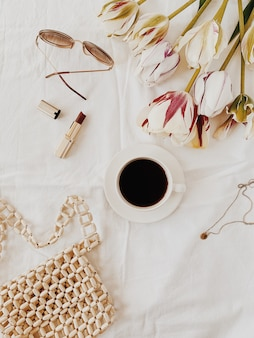 Een kopje koffie liggend op bed met witte lakens, tulpen, rode lippenstift, bril, kleingeld en ketting