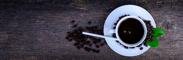 Een kopje koffie met bonen en bladeren op het zwarte hout. bovenaanzicht.