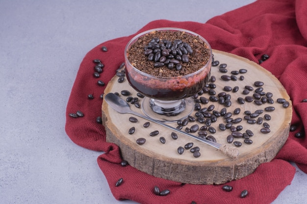 Een kopje koffie met chocoladebonen op een houten bord.