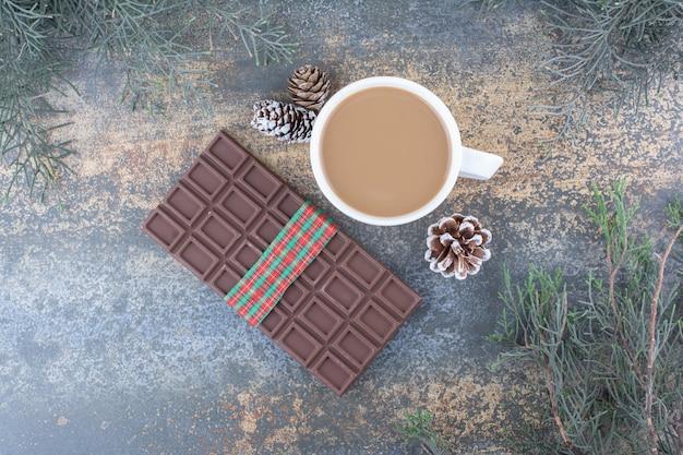 Een kopje koffie met dennenappels en chocolade. hoge kwaliteit foto