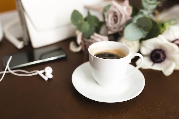 Een kopje koffie met een boeket malse anemoon, eucalyptustakken en pastel paarse rozen, een dameshandtas, koptelefoon en een telefoon op een bruine houten tafel.