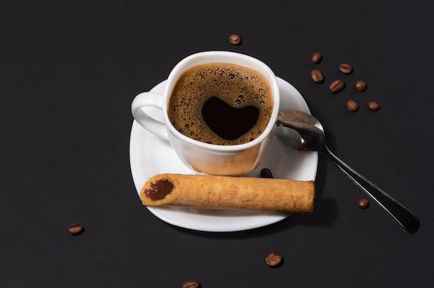 Een kopje koffie met een hartje en een krokant wafelbuisje gevuld met gekookte gecondenseerde melk